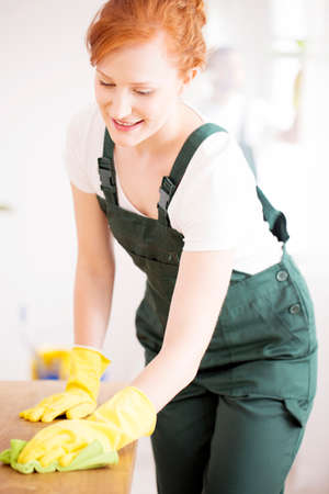 Close-up of smiling woman in green overalls and yellow gloves cleaning a table 版權商用圖片