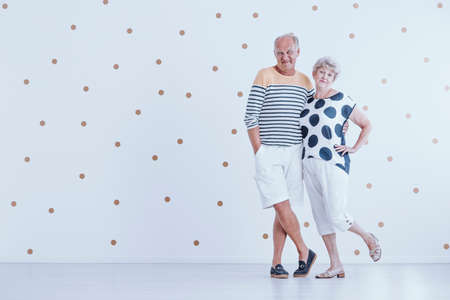 Photo with copy space of couple of elders smiling and standing in an empty room with dotted wall