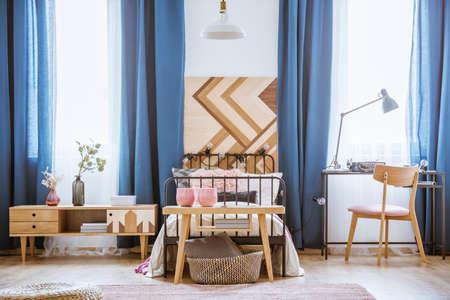 ティーンエイジャーの寝室のインテリアに食器棚と椅子が置いたベッドの前の木製のテーブルの上のピンクの花瓶 写真素材