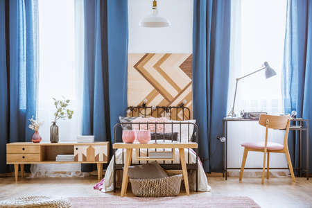 Pink vases on wooden table in front of a bed with lights in teenager's bedroom interior with cupboard and chair at desk