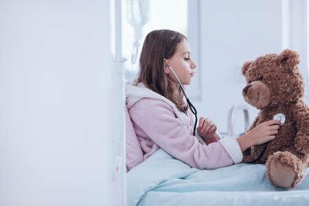 Sick girl in pink bathrobe examining a teddy bear using stethoscope in the hospital