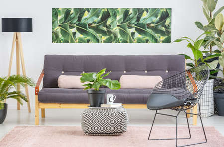 Black chair next to patterned pouf with plant in bright living room interior with dark sofa against white wall with green poster Stock Photo