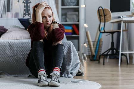Zmartwiona, młoda dziewczyna trzymająca się za głowę, mrucząca na podłodze w swojej sypialni