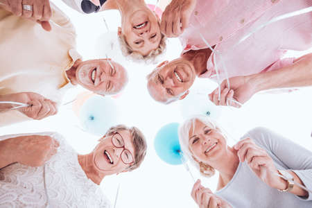 Group of smiling seniors looking down and holding balloons