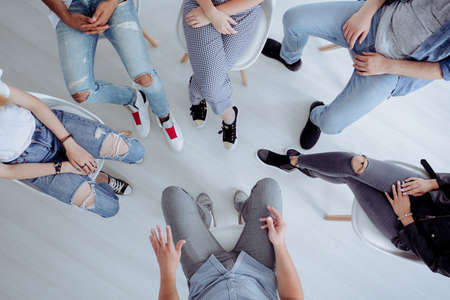 High angle of rehab specialist and rebellious teenagers sitting in a circle during a meeting