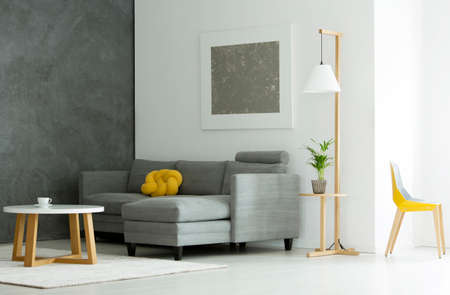 Plant on wooden stool under lamp next to sofa in grey flat interior with round table and yellow chair