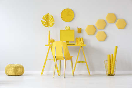 Pouf next to chair at desk with monstera leaf against white wall with honeycombs in yellow room interior