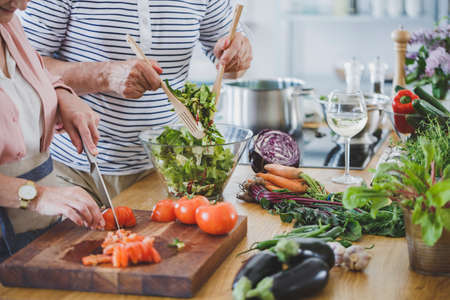Close-up of senior people cutting tomatoes and mixing salad while preparing healthy dinner Standard-Bild