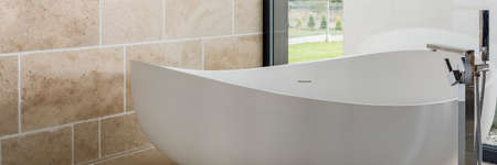 Beige glaze in simple bathroom with white shapely bathtub and stainless steel faucet