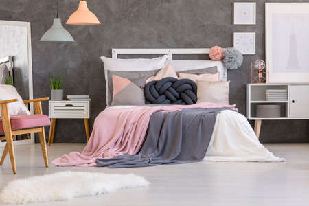 Stock Photo   White Fur Near Bed With Pink And Grey Bedsheets In Cozy  Bedroom Interior With Lamps And Posters