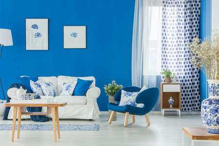 Blue armchair and white couch in living room interior with flowers, posters and wooden table 写真素材 - 96587492