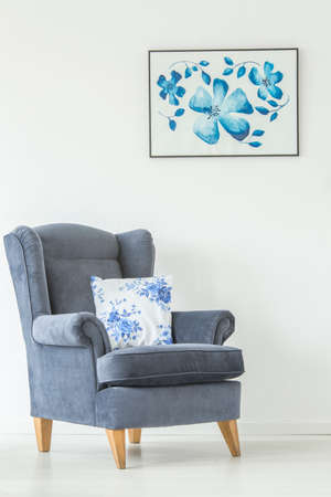 Floral cushion on armchair against white wall with flowers poster in bright living room interior Reklamní fotografie