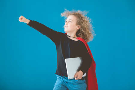 Young boy as superhero with notebook against blue background