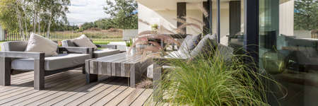 Wooden garden furniture on terrace with a floor constructed of wood boards Stock Photo