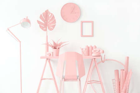 Desk with fern and telephone against white wall with clock and empty frame in pink workspace interior with chair