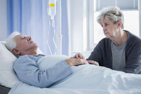 Worried wife taking care of sick man lying connected to a drip