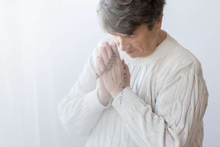 Religious senior person praying with rosary against white background with copy space