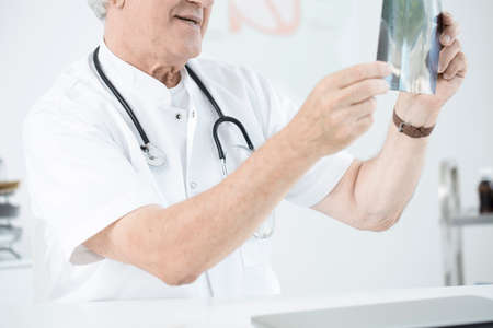 Cropped photo of a senior doctor looking closely at an x-ray Stock Photo