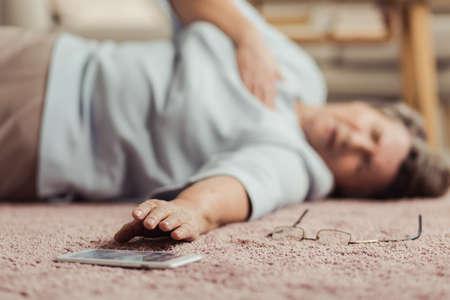 Ältere Person mit Herzinfarkt erreichen das Telefon zum Hören für Hilfe Standard-Bild