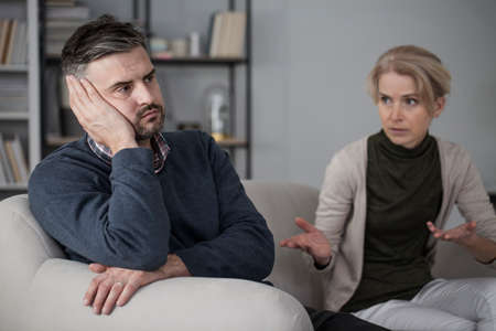 Upset man refusing to listen to his constantly complaining wife Stock Photo