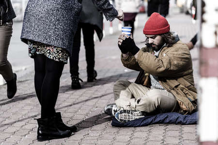 Woman giving money to a homeless man sitting on the pavement and holding a cup Stock Photo