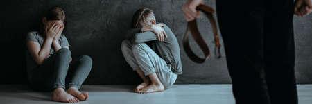 Terrified children afraid of an aggressive parent holding a belt 写真素材 - 96784150