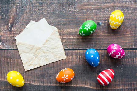 Old envelope with letter and colorful easter eggs