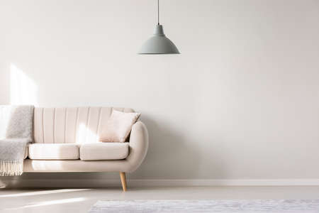 Beige sofa against white, empty wall with copy space in simple living room interior with lamp Фото со стока