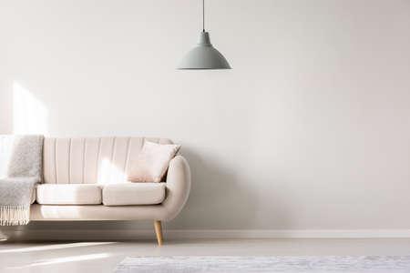 Beiges Sofa gegen weiße, leere Wand mit Kopienraum im einfachen Wohnzimmerinnenraum mit Lampe Standard-Bild - 96627774
