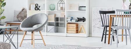木製のダイニングテーブルに塗装された椅子と、食器棚に装飾が施された居心地の良いフラットなインテリアの灰色のアームチェア 写真素材