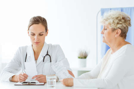 Worried doctor looking at bad results of medical examinations during patients visit
