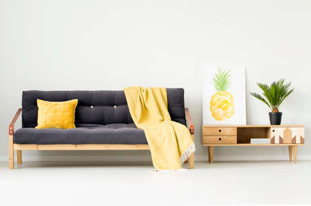 Warm living room interior with pineapple poster on a wooden cupboard and yellow blanket on black couch Zdjęcie Seryjne - 96637561