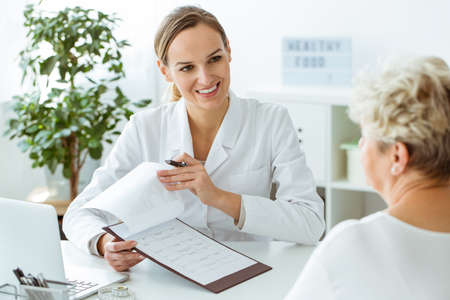 High angle of smiling doctor showing good results of medical examinations to the patient