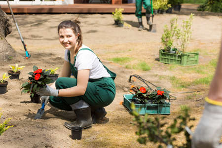 Smiling young gardener in dungarees and wellingtons, planting flowers Stock Photo
