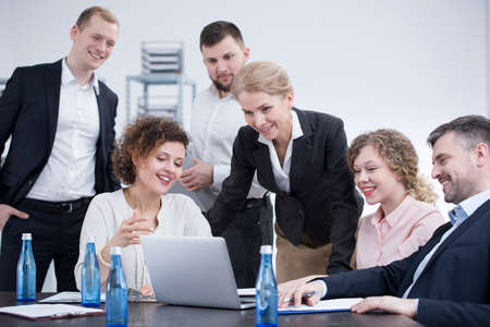 Smiling employees in suits brainstorming during a team meeting in the company