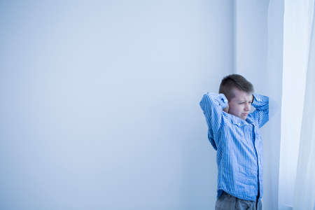 Young autistic boy in a white, empty room standing next to a window covering his ears Stock Photo