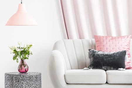金属製の隣に立つ白いソファのパステルクッション、リビングルームのインテリアにバラが付いたサイドテーブル 写真素材