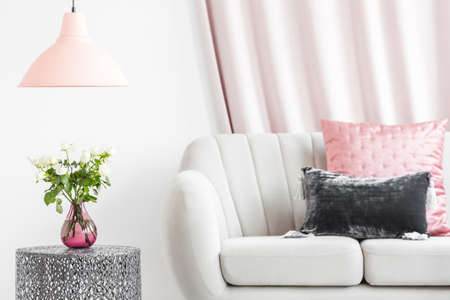 Pastel cushions on white sofa standing next to a metal, side table with roses in a living room interior