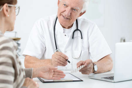 Enthusiastic doctor showing a new medicine to his hopeful patient