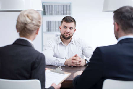 Self-confident man listening to recruiters during a job interview in corporation Stock Photo - 96632494