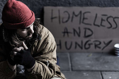 Homeless, slovenly man sitting on the sidewalk with a sign behind him