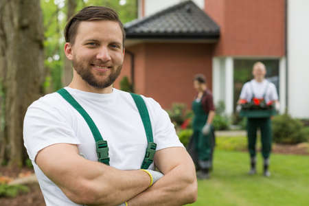Portrait of a muscled smiling gardener in a white t-shirt Stock Photo