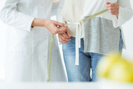 Close-up of doctor showing measurement on yellow tape to the patient Stock Photo