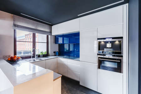 Oven built in white cabinets and blue glaze in modern kitchen interior with window Фото со стока
