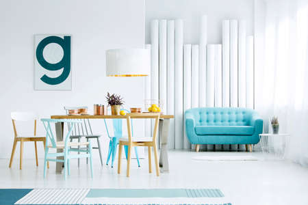 Simple poster hanging on white wall in dining room interior with wooden table, blue sofa and decorative tubes