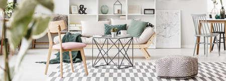 Puf, mesa y silla de madera sobre alfombra estampada cerca de sofá beige con manta verde en el luminoso salón interior