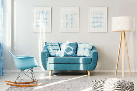 Blue settee between white lamp and rocking chair in living room interior with gallery of posters