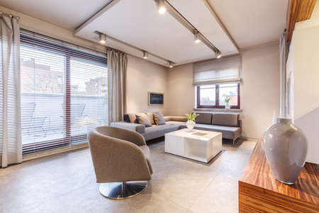 Lights in spacious, beige apartment interior with windows, grey armchair and white table 写真素材