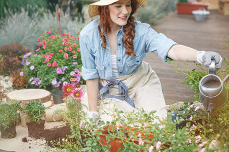 Pretty girl in a straw hat on her head, watering flowers in a garden full of colorful plants