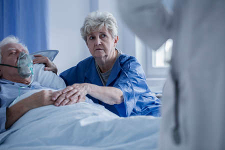 Elderly woman supporting sick man with oxygen mask while talking with the doctor